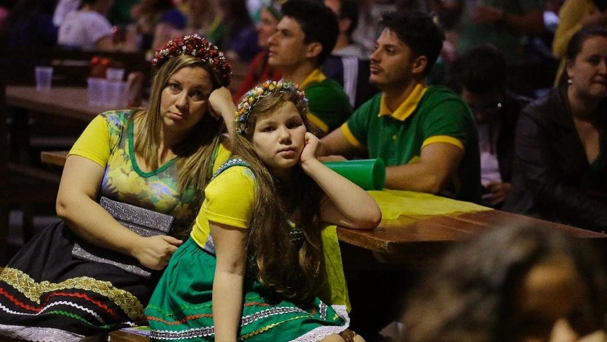 Brazilians of German descent watch Brazil lose 7-1 to Germany at a World Cup semifinal match on TV in Blumenau, Brazil, Tuesday, July 8, 2014. The German community in southern Brazil organized an Oktoberfest party to watch the Brazil vs. Germany match. (AP Photo/Nelson Antoine)