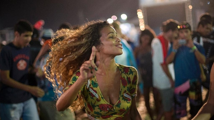 A Brazilian woman dances during the World Cup Fan Fest 2014, on Copacabana beach, in Rio de Janeiro, Brazil, Wednesday, July 9, 2014. Brazil has a demographic imbalance between men and women, the result of higher mortality rates among young men, which is particularly acute in Rio de Janeiro, where there are just over 9 men for every 10 women, according to the 2010 census. (AP Photo/Silvia Izquierdo)