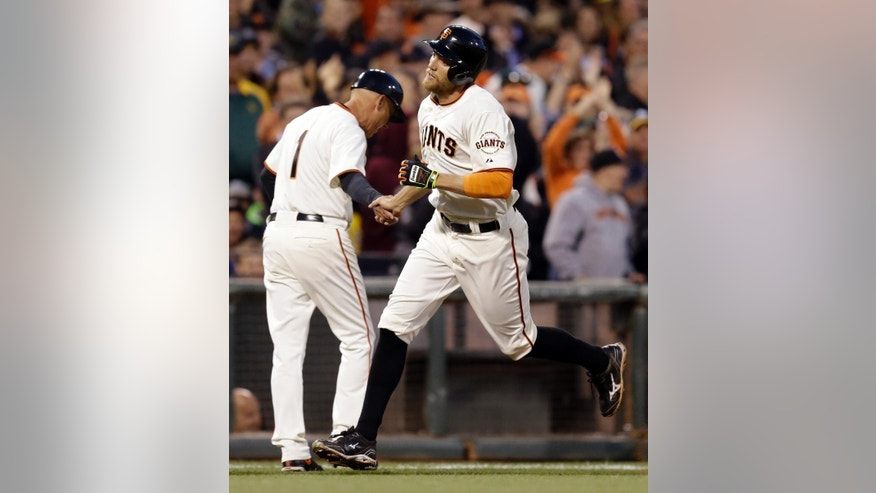 San Francisco Giants' Hunter Pence, right, is congratulated by third base coach Tim Flannery after Pence hit a home run off Oakland Athletics' Jason Hammel in the fourth inning of a baseball game Wednesday, July 9, 2014, in San Francisco. (AP Photo/Ben Margot)