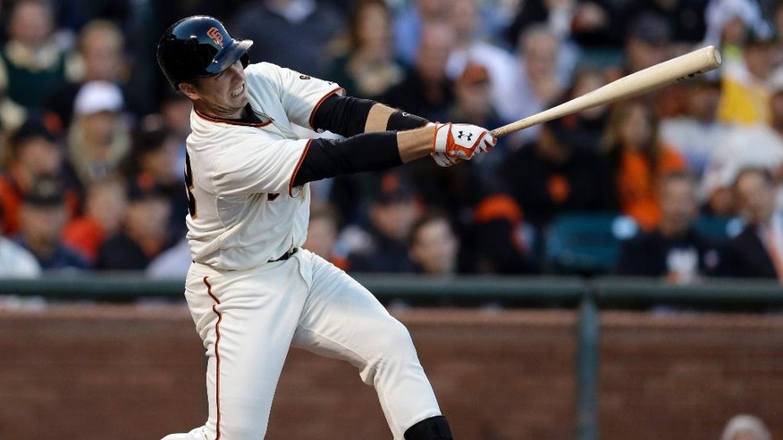 San Francisco Giants' Buster Posey swings for an RBI single off Oakland Athletics' Jason Hammel in the third inning of a baseball game Wednesday, July 9, 2014, in San Francisco. (AP Photo/Ben Margot)