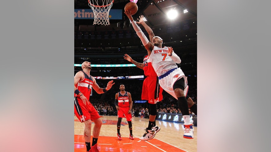 FILe - In this Dec. 16, 2013 file photo, New York Knicks' Carmelo Anthony (7) goes to the basket against Washington Wizards' Trevor Booker (35) during the first half of an NBA basketball game in New York. Signing day has arrived in the NBA, if the biggest free agents care to grab their pens. But it's unclear if Carmelo Anthony, Chris Bosh and Dwyane Wade _ who all might be waiting on LeBron James to go first _ are ready.(AP Photo/Jason DeCrow, File)