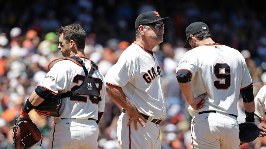 San Francisco Giants manager Bruce Bochy, center, stands on the mound with catcher Buster Posey, left, and first baseman Brandon Belt, right, during a pitching change after the Oakland Athletics scored their sixth run in the sixth inning of their interleague baseball game Thursday, July 10, 2014, in San Francisco. Bochy was relieving relief pitcher Javier Lopez. (AP Photo/Eric Risberg)