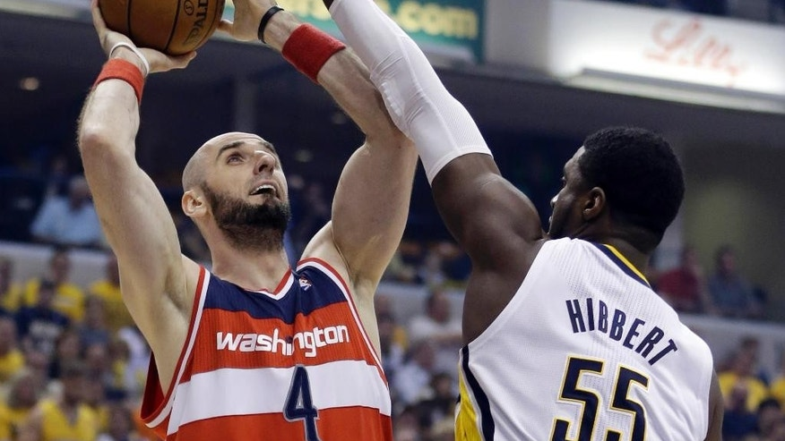 FILE - This May 13, 2014 file photo shows Washington Wizards center Marcin Gortat, left, shooting over Indiana Pacers center Roy Hibbert during the first half of game 5 of the Eastern Conference semifinal NBA basketball playoff series in Indianapolis. Gortat has signed his five-year, $60 million contract to remain with the Washington Wizards. The Wizards announced Thursday that the Polish center had signed the deal on the first day permitted under NBA free agency rules. (AP Photo/Darron Cummings, File)