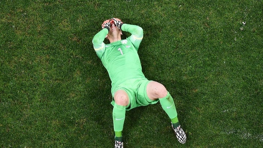 Netherlands' goalkeeper Jasper Cillessen lies on the pitch after losing to Argentina in a World Cup semifinal soccer match at the Itaquerao Stadium in Sao Paulo, Brazil, Wednesday, July 9, 2014. Argentina beat the Netherlands 4-2 in a penalty shootout to reach the World Cup final against Germany. (AP Photo/Francois Xavier Marit, Pool)