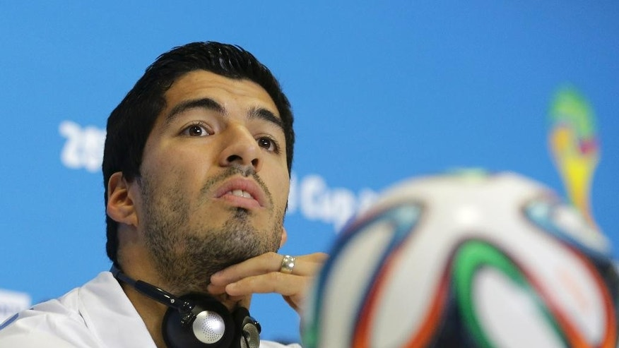 FILE - In this June 23, 2014 file photo, Uruguay's Luis Suarez listens to a question during a press conference at the Arena das Dunas in Natal, Brazil. Suarez was banned for nine competitive international matches, four months from all football and fined for biting Italy's Giorgio Chiellini's shoulder during their group D World Cup soccer match. Football's international governing body on Thursday, July 10, 2014, said its appeals committee rejected Suarez's appeal against his ban for biting his opponent. (AP Photo/Antonio Clanni, File)