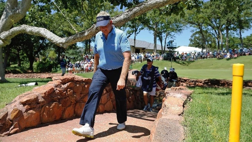 Colin Montgomerie walks to the fifth tee during the second round of the U.S. Senior Open golf tournament at Oak Tree National in Edmond, Okla., Friday, July 11, 2014. (AP Photo/Sue Ogrocki)