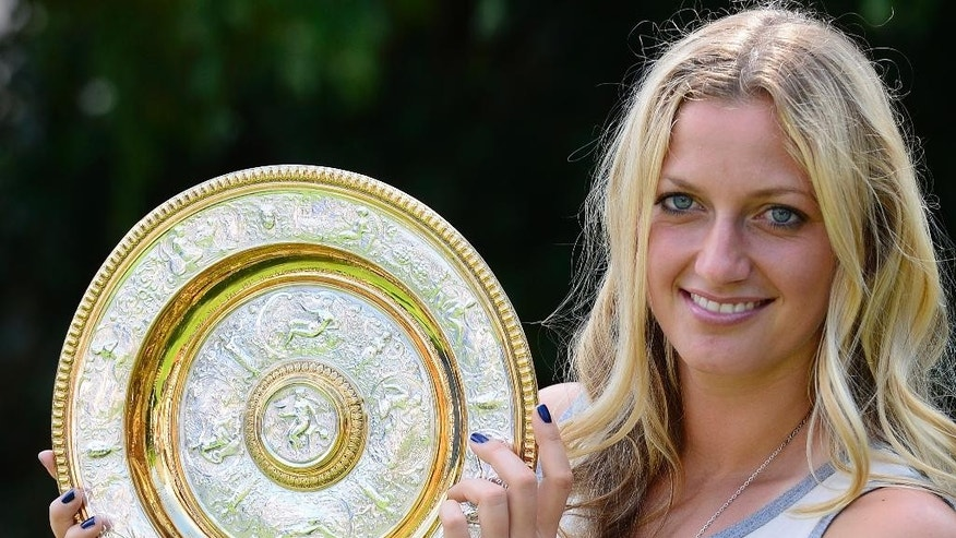 Czech tennis player Petra Kvitova holds the trophy of the All England Lawn Tennis Championships in Wimbledon at the press conference in Prague, Monday, July 7, 2014. She won the women's singles final against Eugenie Bouchard of Canada.  (AP Photo,CTK/Roman Vondrous)    SLOVAKIA OUT