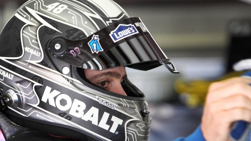 Driver Jimmie Johnson gets ready to climb into his car during practice for Sunday's NASCAR Sprint Cup series auto race at New Hampshire Motor Speedway, Friday, July 11, 2014, in Loudon, N.H. (AP Photo/Jim Cole)