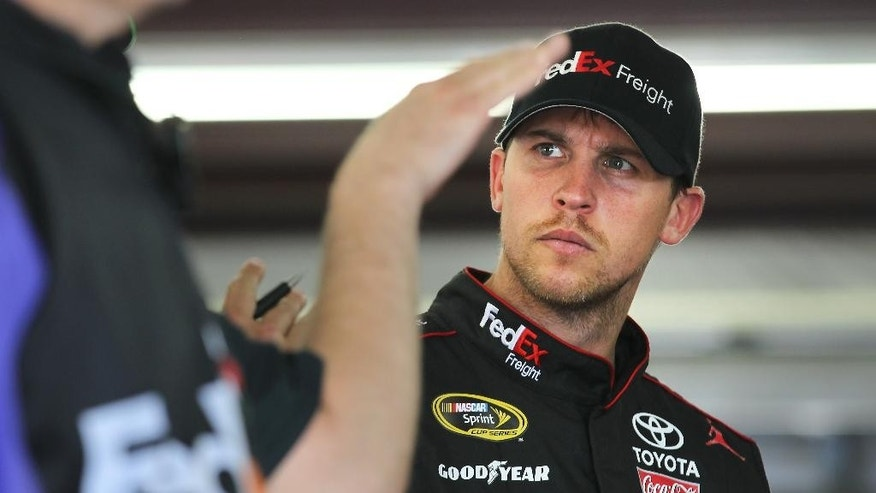 Driver Denny Hamlin listens a member of his team talks before practice, Friday, July 11, 2014 in Loudon, N.H., for Sunday's NASCAR Sprint Cup Series Auto Race race at New Hampshire Motor Speedway. (AP Photo/Cheryl Senter)