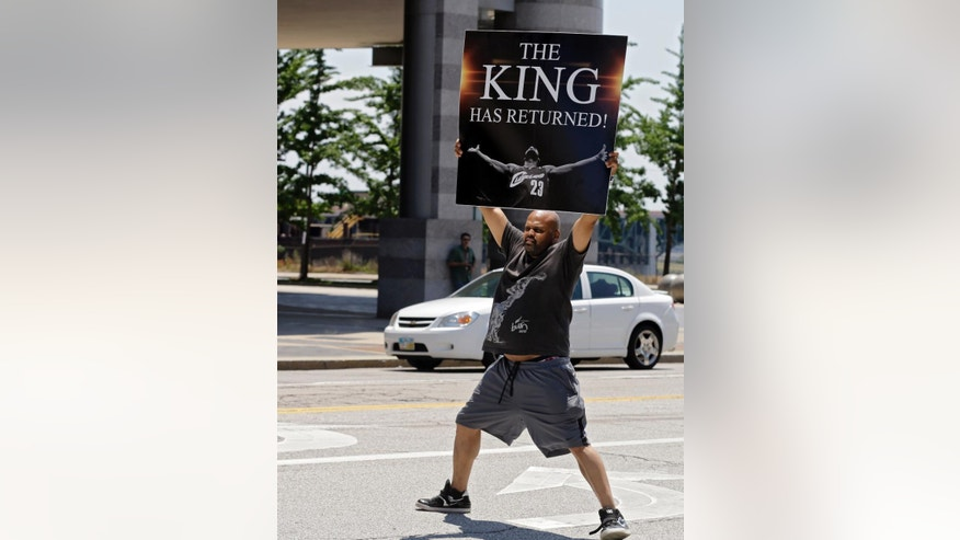 Graphic designer Alvin Smith holds up a poster in the street outside Quicken Loans Arena in Cleveland Friday, July 11, 2014,  heralding the return of NBA basketball star LeBron James. James, who left the Cavaliers four years ago to join the Miami Heat, announced earlier he would return to the Cavaliers. (AP Photo/Mark Duncan)