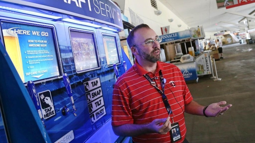 In this July 8, 2014, photo, Pete Spike, general manager for Delaware North  Companies Sportservice, talks about the newly launched self-service beer kiosks at Target Field, home of the Minnesota Twins and the upcoming All-Star game, in Minneapolis. (AP Photo/Jim Mone)