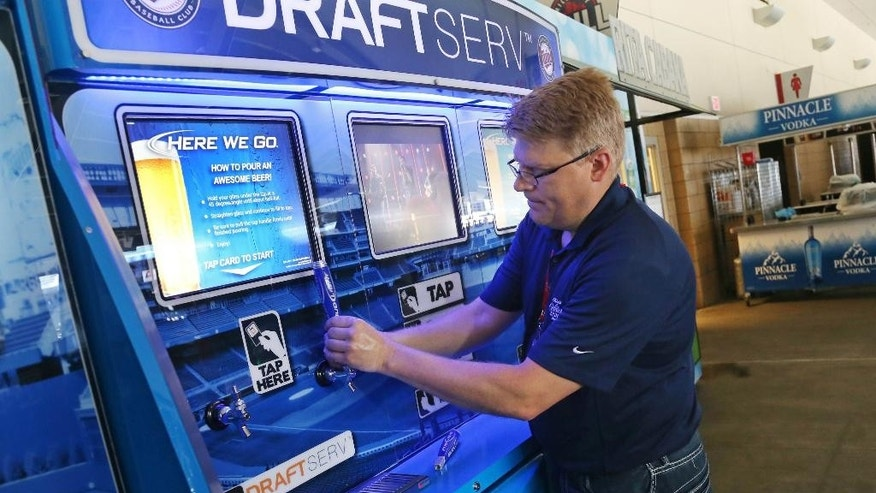 In this July 8, 2014, photo, Tom Cartwell attaches the handles to the newly launched self-service beer kiosks at Target Field, home of the Minnesota Twins and the upcoming All-Star game, in Minneapolis. (AP Photo/Jim Mone)