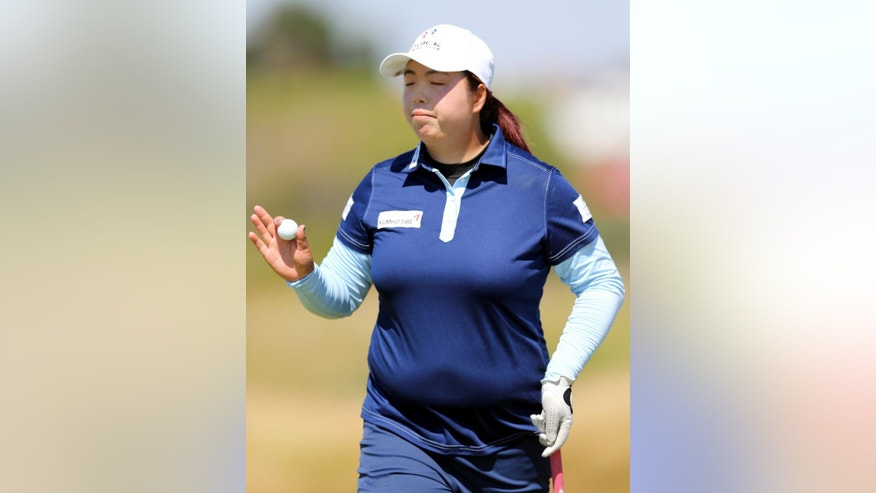 China's Shanshan Feng holds up her ball after a putt on the 9th green during the second day of the Women's British Open golf championship on the Royal Birkdale Golf Club, Southport, England, Friday July 11, 2014. (AP Photo/Scott Heppell)