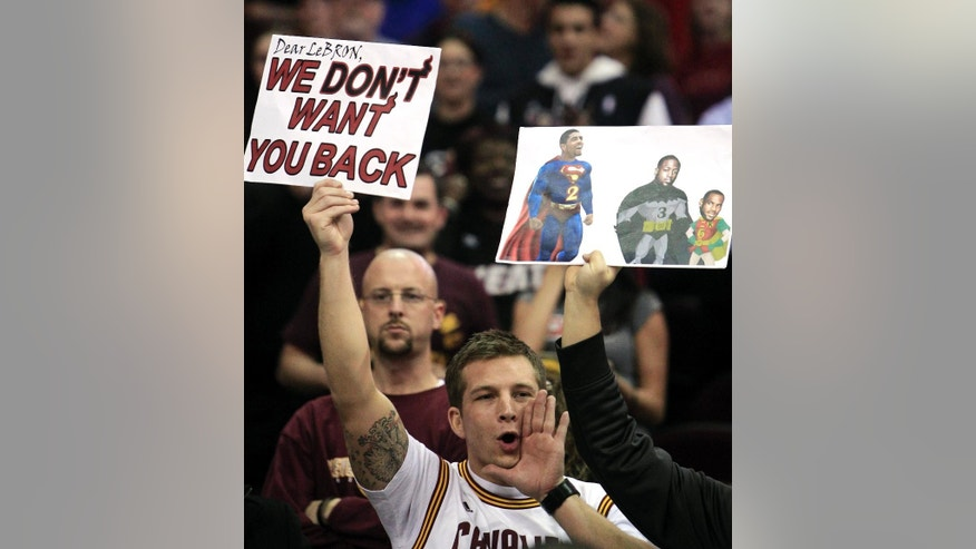 FILE - In this Feb. 17, 2012, file photo, a Cleveland Cavaliers holds a sign and yells as Miami Heat's LeBron James is introduced before andanNBA basketball game against Cavaliers in Cleveland. James told Sports Illustrated on Friday, July 11, 2014, he is leaving the Miami Heat to go back to the Cleveland Cavaliers. (AP Photo/Tony Dejak, File)