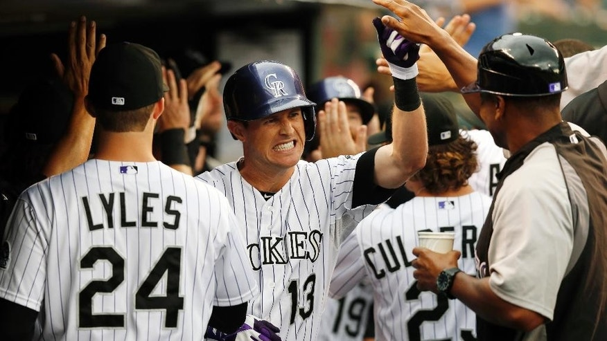 Colorado Rockies' Drew Stubbs (13) is congratulated by teammates in the dugout after hitting a two run home run off Minnesota Twins starting pitcher Kris Johnson during the first inning of a baseball game on Friday, July 11, 2014, in Denver. (AP Photo/Jack Dempsey)