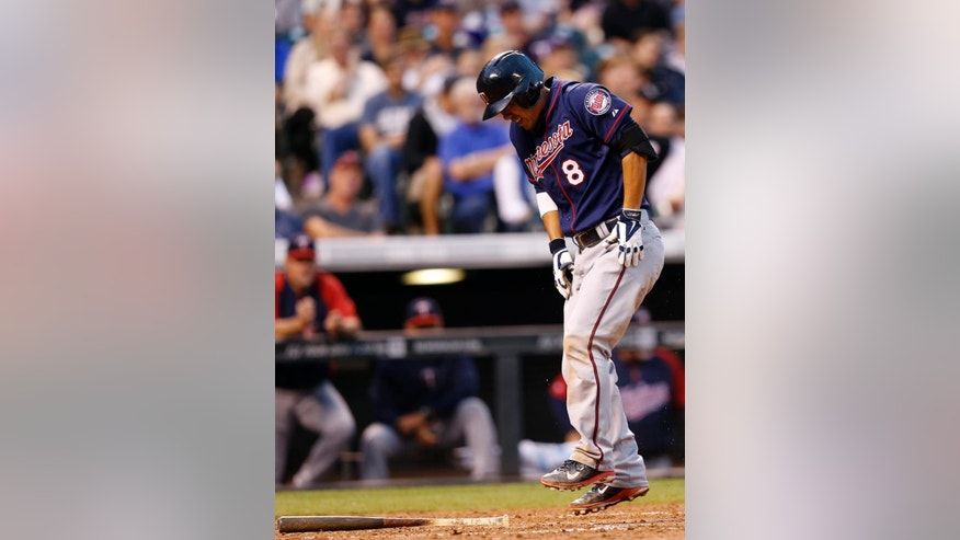 Minnesota Twins' Kurt Suzuki reacts after hitting a foul ball off against the Colorado Rockies during the fifth inning of a baseball game on Friday, July 11, 2014, in Denver. (AP Photo/Jack Dempsey)