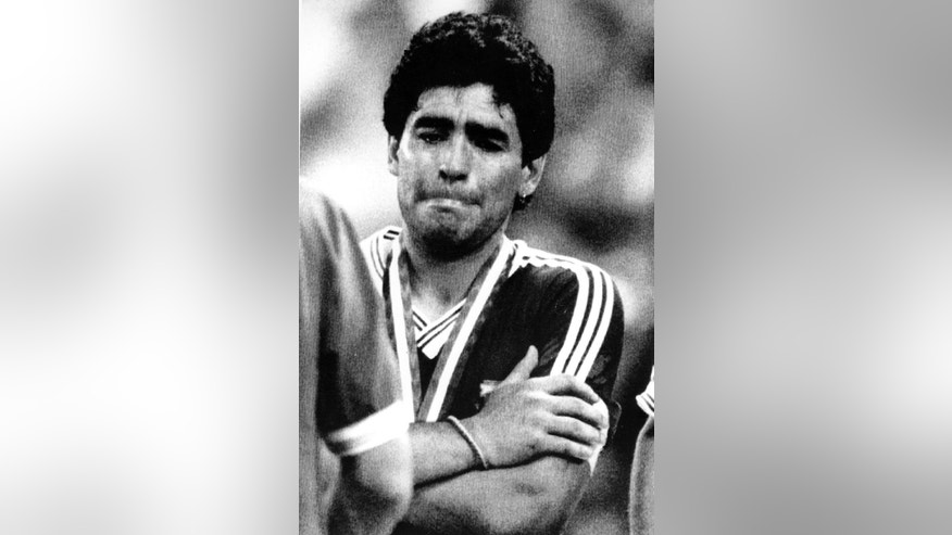 FILE - The July 8, 1990 file photo shows Agentina's Diego Maradona, his arms crossed, fighting his tears back at the end of the Soccer World Cup final game in Rome, Italy, when Germany defeated Argentina 1-0. On Sunday, July 13, 2014, Germany and Argentina will face each other again in the final of the 2014 soccer World Cup.(AP-Photo/Kalle Tornstrom, file)