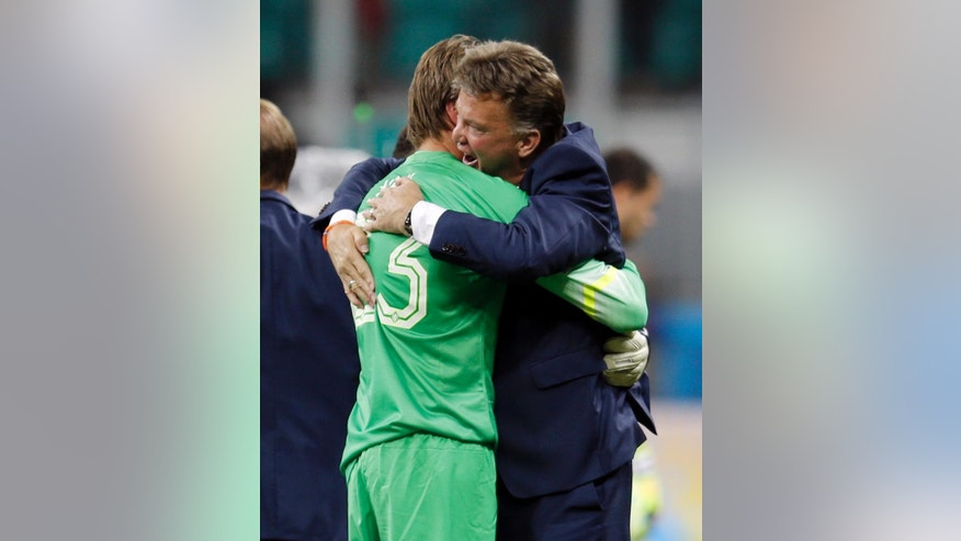 FILE - In this July 5, 2014 file photo, Netherlands head coach Louis van Gaal hugs goalkeeper Tim Krul after the Netherlands defeated Costa Rica 4-3 in a penalty shootout after a 0-0 tie at a World Cup quarterfinal soccer match in Salvador, Brazil. With the Netherlands and Costa Rica scoreless after 120 minutes, Dutch coach Louis van Gaal made an astounding call in the final seconds of their quarterfinal: He replaced his first-choice goalkeeper with his understudy, Tim Krul. The masterstroke made Van Gaal look like a football genius, whetting the appetite of fans of Manchester United, his next stop as coach. (AP Photo/Natacha Pisarenko, File)