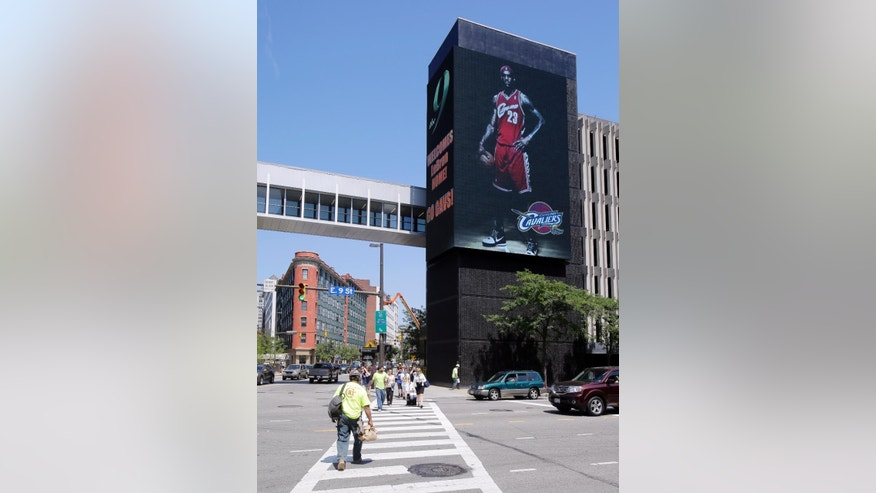 Pedestrians cross East 9th Street in Cleveland under a large electronic billboard featuring NBA basketball star LeBron James in his old Cleveland Cavaliers uniform Friday, July 11, 2014. Earlier James announced he would return to Cleveland, where he played seven years before leaving for the Miami Heat. (AP Photo/Mark Duncan)