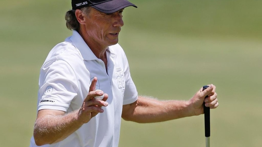 Bernhard Langer waves to the crowd after his putt on the first green during the third round of the U.S. Senior Open golf tournament at Oak Tree National in Edmond, Okla., Saturday, July 12, 2014. (AP Photo/Sue Ogrocki)
