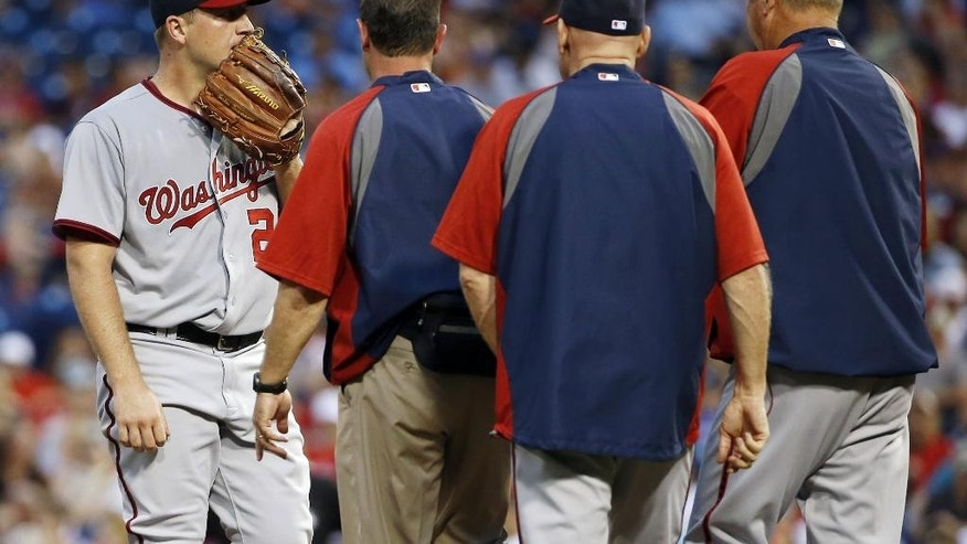Washington Nationals starting pitcher Jordan Zimmermann, left, talks with team personnel on the mound during the fourth inning of a baseball game against the Philadelphia Phillies, Friday, July 11, 2014, in Philadelphia. Zimmermann left the game after the conference. (AP Photo/Matt Slocum)