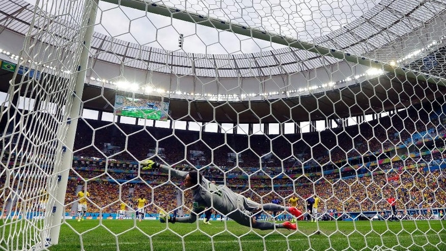 Brazil's goalkeeper Julio Cesar dives in an attempt to stop a shot by Netherlands' Robin van Persie, who scored his team's first goal on a penalty shot during the World Cup third-place soccer match between Brazil and the Netherlands at the Estadio Nacional in Brasilia, Brazil, Saturday, July 12, 2014. (AP Photo/Andre Penner)