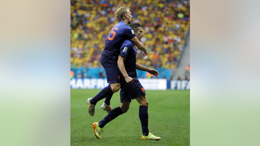 Netherlands' Robin van Persie, right, celebrates with his teammate Dirk Kuyt after scoring his team's first goal on a penalty shot during the World Cup third-place soccer match between Brazil and the Netherlands at the Estadio Nacional in Brasilia, Brazil, Saturday, July 12, 2014. (AP Photo/Natacha Pisarenko)