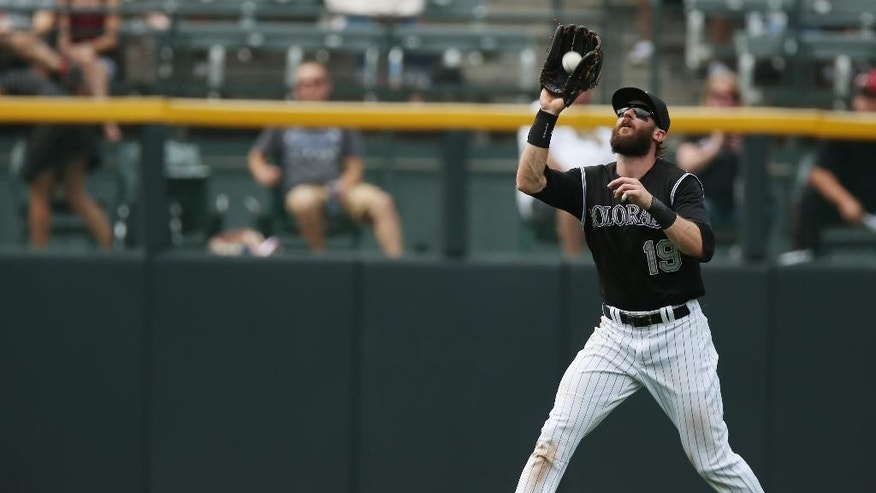 Colorado Rockies centerfielder Charlie Blackmon fields fly ball off the bat of Minnesota Twins' Sam Fuld in the fourth inning of an interleague baseball game in Denver on Saturday, July 12, 2014. (AP Photo/David Zalubowski)