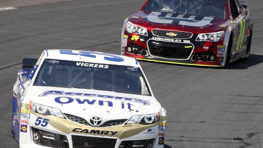 Driver Brian Vickers races ahead of Jeff Gordon during the final practice before Sunday's Sprint Cup Series auto race at New Hampshire Motor Speedway, Saturday, July 12, 2014, in Loudon, NH (AP Photo/Jim Cole)