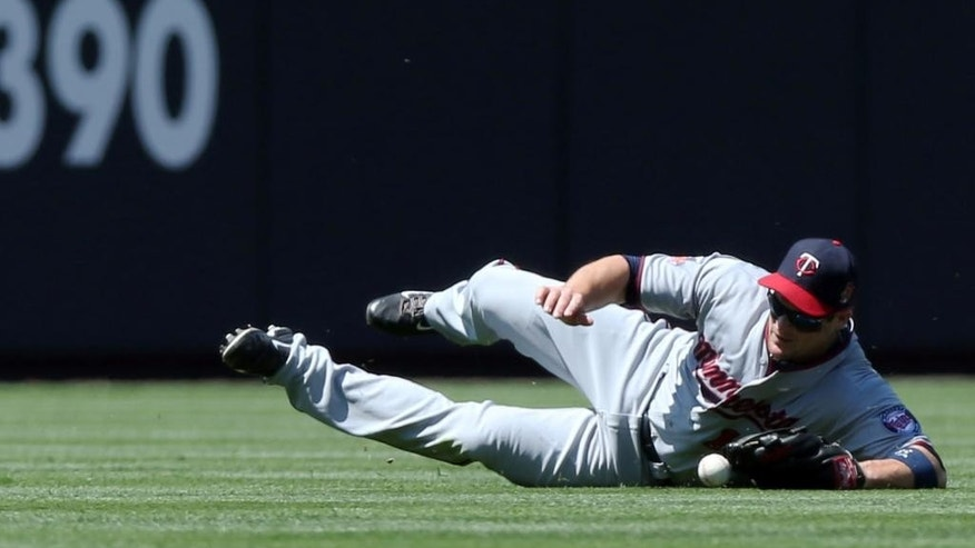 Minnesota Twins left fielder Josh Willingham dives but misses a ball that went for a double  by Colorado Rockies' Nolan Arenado in the first inning of an interleague baseball game in Denver on Sunday, July 13, 2014. (AP Photo/David Zalubowski)
