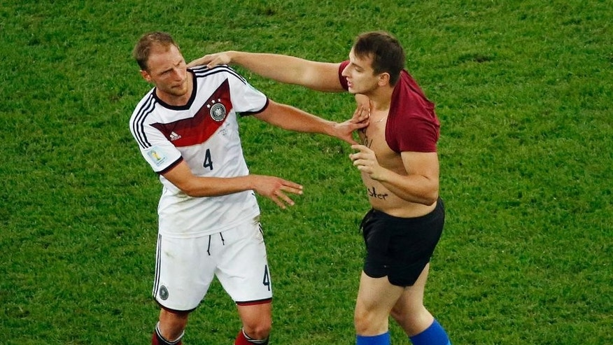 Germany's Benedikt Hoewedes faces a man who run into the pitch during the World Cup final soccer match between Germany and Argentina at the Maracana Stadium in Rio de Janeiro, Brazil, Sunday, July 13, 2014. (AP Photo/Fabrizio Bensch, Pool)