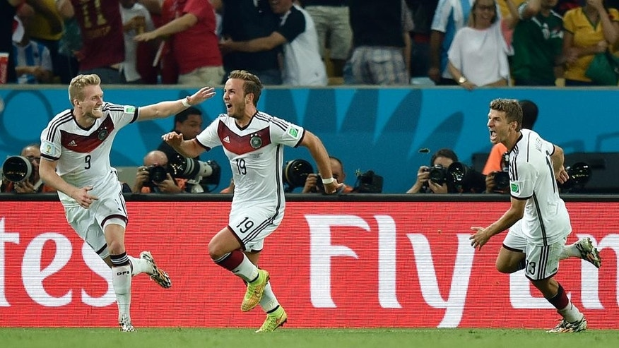 Germany's Mario Goetze, center, celebrates with Andre Schuerrle (9) after Goetze scored the opening goal during the World Cup final soccer match between Germany and Argentina at the Maracana Stadium in Rio de Janeiro, Brazil, Sunday, July 13, 2014. At right is Thomas Mueller (13). (AP Photo/Martin Meissner)
