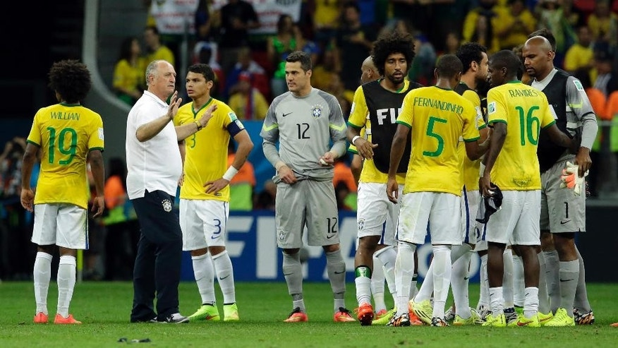 Brazil's coach Luiz Felipe Scolari, second left, stands with his players after the World Cup third-place soccer match between Brazil and the Netherlands at the Estadio Nacional in Brasilia, Brazil, Saturday, July 12, 2014. The Netherlands won the match 3-0. (AP Photo/Hassan Ammar)