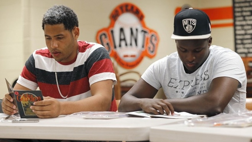 In this May 22, 2014 photo, San Francisco Giants baseball prospects Jose Murel and Sandy Perez, right, read beginner English books in class in Scottsdale, Ariz. San Francisco is just one of many clubs putting a stronger emphasis on teaching English basics, including training as to writing checks, using a bank account or mailing a letter. (AP Photo/Matt York)