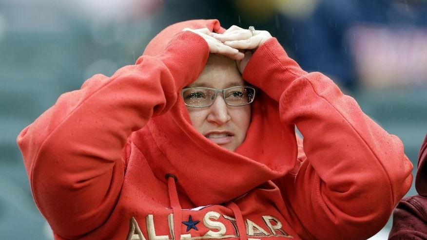 A fan watches in the rain during National League batting practice for the MLB All-Star baseball game, Monday, July 14, 2014, in Minneapolis. (AP Photo/Jeff Roberson)