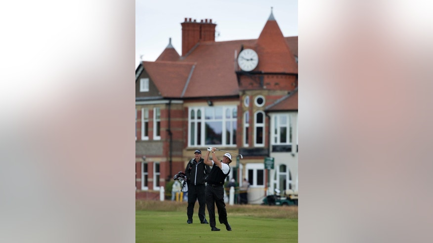 Phil Mickelson of the US plays a shot on the 3rd fairway with the clubhouse in the background during a practice round at Royal Liverpool Golf Club prior to the start of the British Open Golf Championship, in Hoylake, England, Monday, July 14, 2014. The 2014 Open Championship starts on Thursday, July 17. (AP Photo/Jon Super)