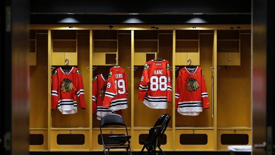 Chicago Blackhawks jerseys of Jonathan Toews (19) and Patrick Kane (88) hang in a locker room before an NHL hockey news conference at the United Center in Chicago, Wednesday, July 16, 2014. The Blackhawks recently agreed to eight-year contract extensions with Toews and Kane.  (AP Photo/Nam Y. Huh)