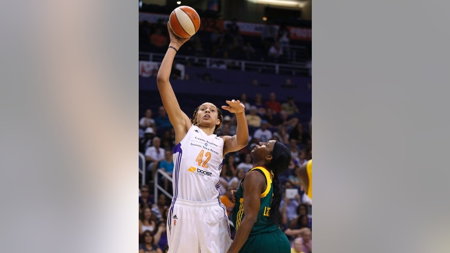 FILE - In this June 3, 2014, file photo, Phoenix Mercury's Brittney Griner, left, shoots over Seattle Storm's Crystal Langhorne during the second half of a WNBA basketball game in Phoenix.  After a difficult first season in the WNBA, the former Baylor star is blossoming into the player everyone thought she would be.  (AP Photo/Ross D. Franklin, File)