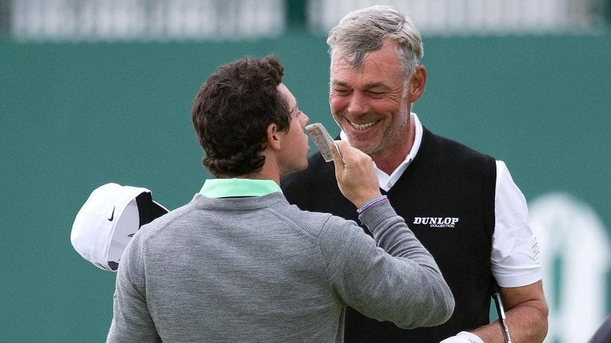 Rory McIlroy, of Northern Ireland, kisses a 20 pound note as Darren Clarke, of Northern Ireland, smiles after winning a wager on the 18th green after holing a putt during a practice round for the British Open Golf championship at the Royal Liverpool golf club, Hoylake, England, Wednesday, July 16, 2014. The British Open Golf championship starts Thursday, July 17. (AP Photo)