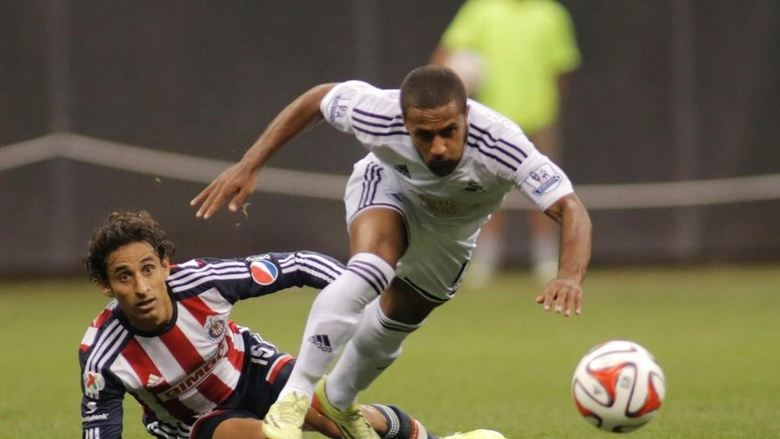 Swansea City's Wayne Routledge, right, chases down the ball against Chivas De Guadalajara's Fernando Arce, left, during the first half of a International League soccer match at Miller Park Wednesday, July 16, 2014, in Milwaukee. (AP Photo/Darren Hauck)