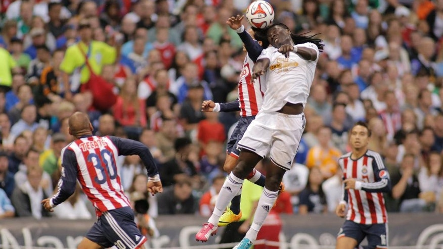 Swansea City's Bafetimbi Gomis, right, goes up for a header against Chivas De Guadalajara's Fernando Arce, left, during the first half of a International League soccer match at Miller Park Wednesday, July 16, 2014, in Milwaukee. (AP Photo/Darren Hauck)