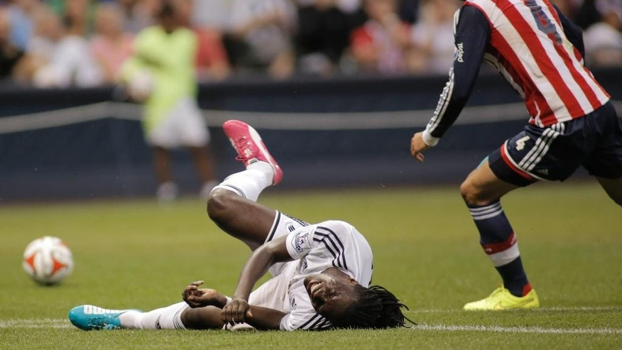 Swansea City's Bafetimbi Gomis, left, grimaces in pain after colliding with Chivas De Guadalajara's Jair Pereira, right, during the first half of a International League soccer match at Miller Park Wednesday, July 16, 2014, in Milwaukee. (AP Photo/Darren Hauck)