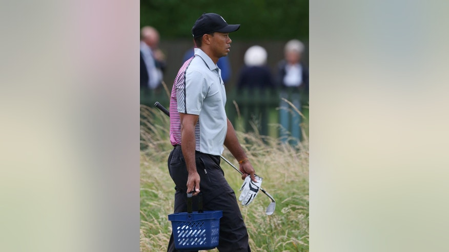 Tiger Woods of the US carries a basket of golf balls toward the practice chipping green ahead of the British Open Golf championship at the Royal Liverpool golf club, Hoylake, England, Wednesday July 16, 2014. The British Open Golf championship starts Thursday July 17. (AP Photo/Jon Super)
