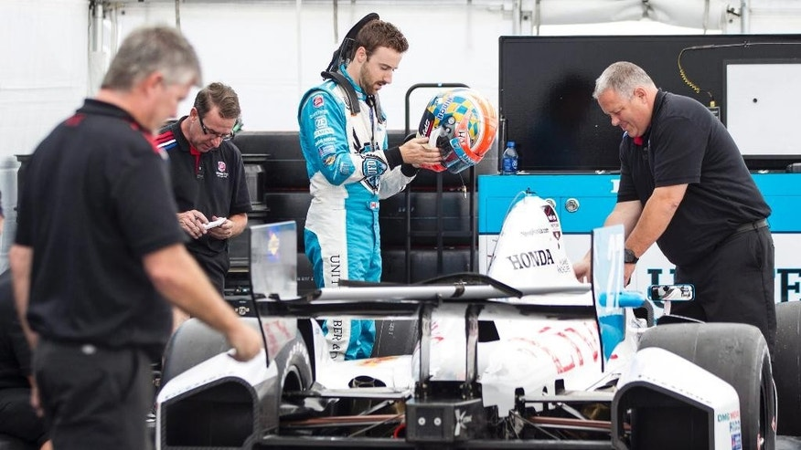 Canadian driver James Hinchcliffe steps into his car as his team prepares to weigh it Thursday, July 17, 2014, ahead of this weekend's IndyCar auto races. (AP Photo/The Canadian Press, Chris Young)