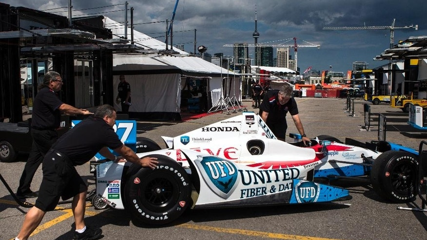 Canadian driver James Hinchcliffe's car is pushed into the team area Thursday, July 17, 2014, ahead of this weekend's IndyCar auto races. (AP Photo/The Canadian Press, Chris Young)