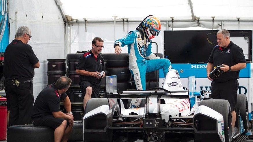 Canadian driver James Hinchcliffe steps into his car as his team prepare to weigh it Thursday, July 17, 2014, ahead of this weekend's IndyCar auto races. (AP Photo/The Canadian Press, Chris Young)