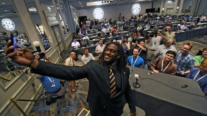Tennessee linebacker AJ Johnson stops to take a selfie during Southeastern Conference NCAA college football media days in Hoover, Ala., on Tuesday, July 15, 2014. (AP Photo/Todd J. Van Emst)