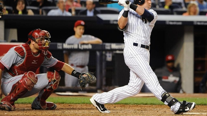 New York Yankees' Jacoby Ellsbury follows through on a two-run home run off of Cincinnati Reds starting pitcher Mike Leake as Devin Mesoraco catches for the Reds in the fifth inning of an interleague baseball game at Yankee Stadium on Friday, July 18, 2014, in New York. (AP Photo/Kathy Kmonicek)