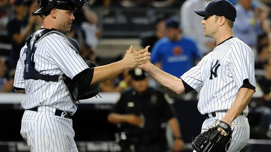 New York Yankees catcher Brian McCann congratulates relief pitcher David Robertson after the Yankees defeated the Cincinnati Reds 4-3 in an interleague baseball game at Yankee Stadium on Friday, July 18, 2014, in New York. (AP Photo/Kathy Kmonicek)