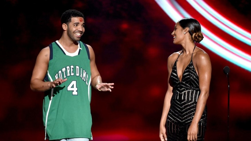 Skylar Diggins, right, smiles at Drake, left, who wears a Notre Dame jersey, at the ESPY Awards at the Nokia Theatre on Wednesday, July 16, 2014, in Los Angeles. Diggins played basketball at Notre Dame. (Photo by John Shearer/Invision/AP)